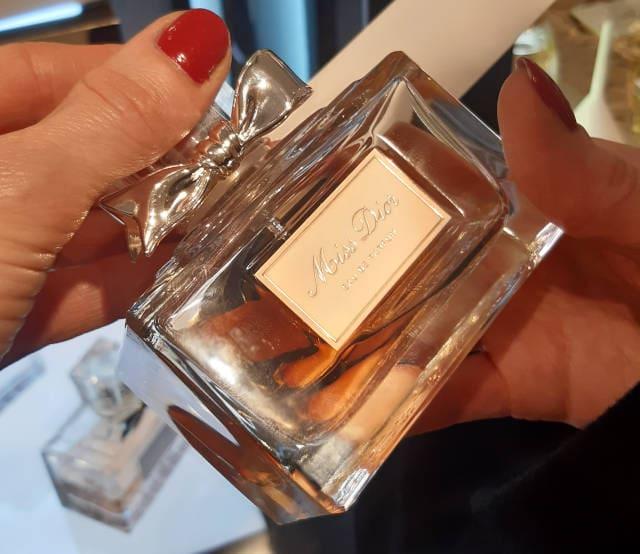 Ingrid holding a bottle of Miss Dior